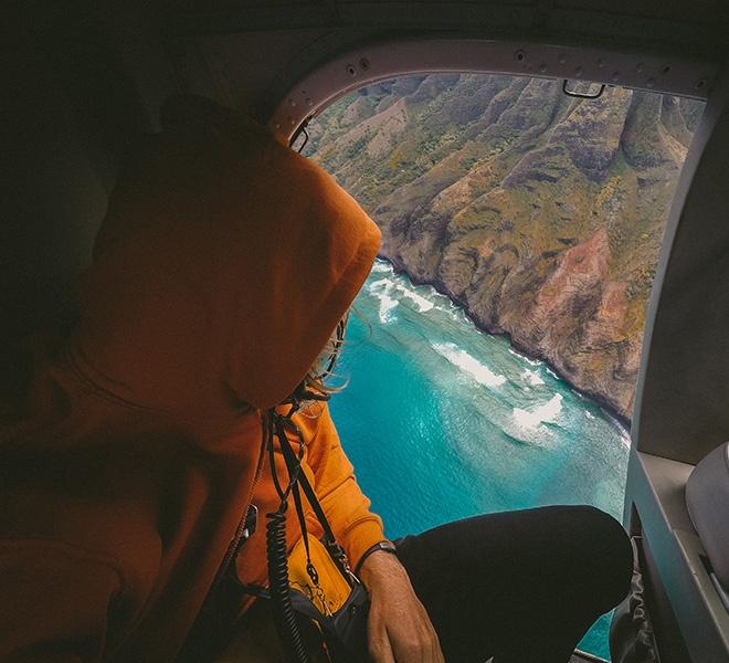 persona volando en un helicóptero viendo el mar
