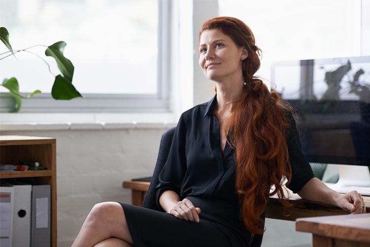 mujer pelirroja sentada con vestido negro