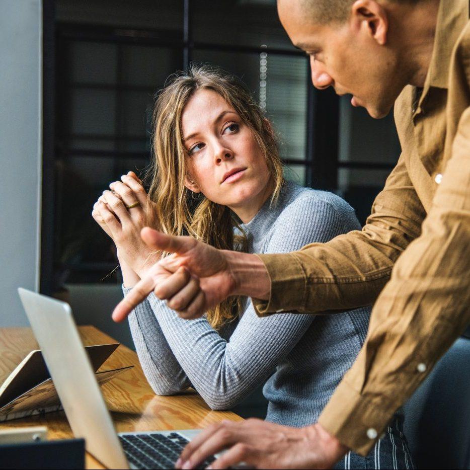 hombre explicando algo con un portátil a una mujer